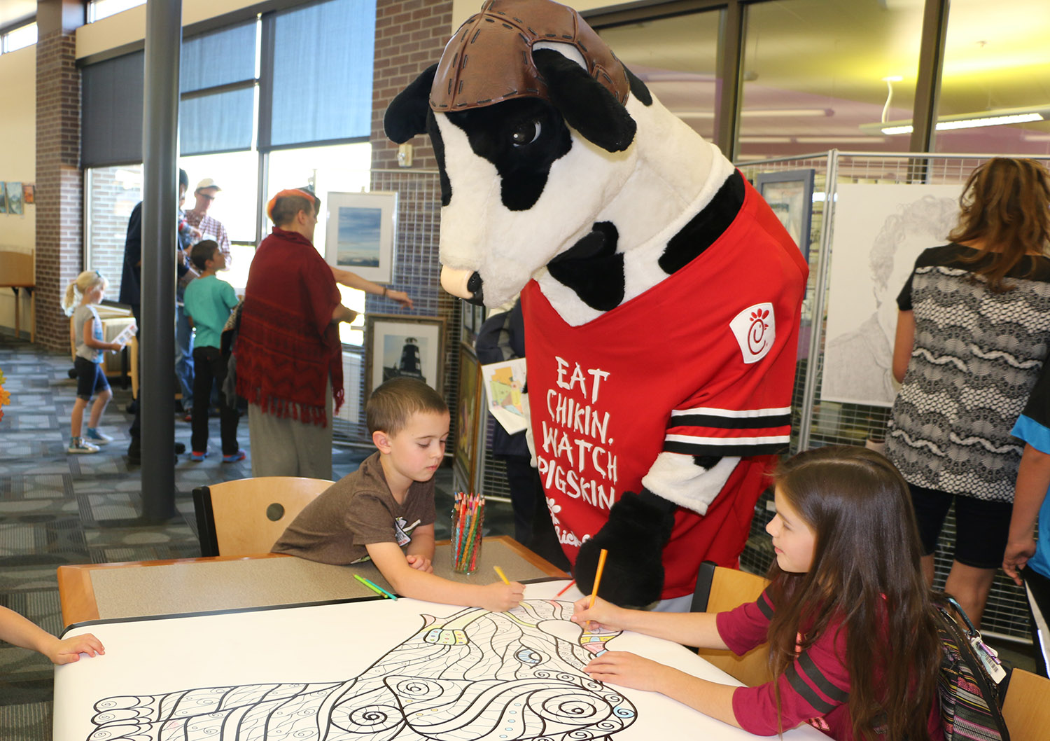 Chick Filet cow watching children color