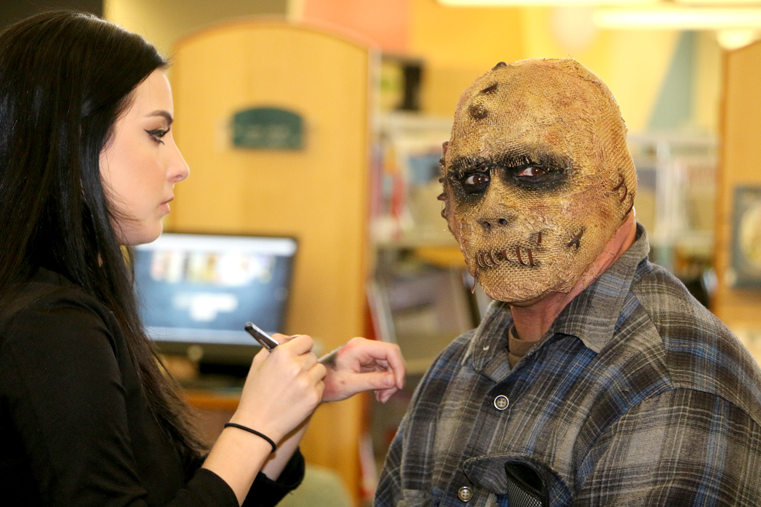 Makeup artist applying a mask to mans face